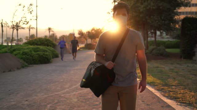 man walking with a bag on a park and wearing a surgical mask during the adaptation to the new normal after confinement during the golden hour - new normal video stock e b–roll