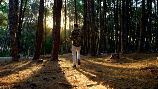 Man walking with bow and arrow in the forest 4k