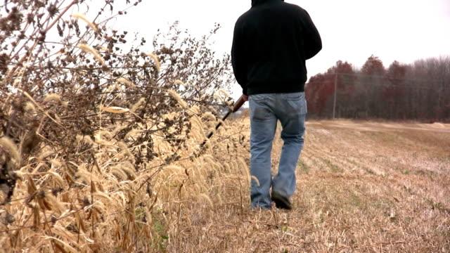 Man Walking with Gun Through Field video