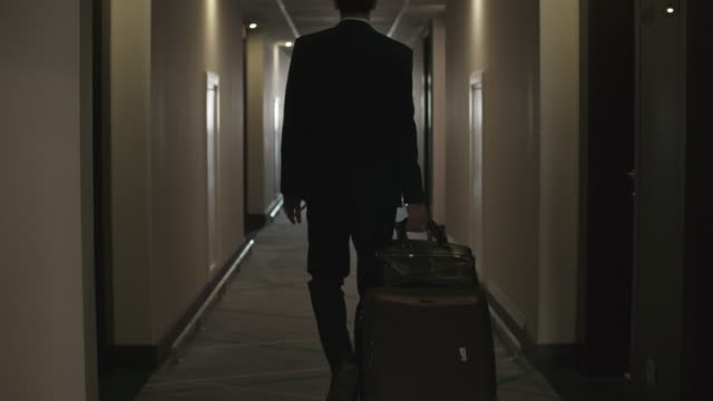 Man Walking with Luggage to Hotel Room Rear view of businessman walking with luggage through corridor to his room in hotel hotel stock videos & royalty-free footage
