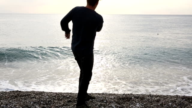 Man walks along deserted beach to sea, skips rock video