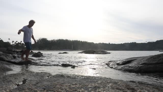 man walks along rocky coastline - solo un uomo maturo video stock e b–roll