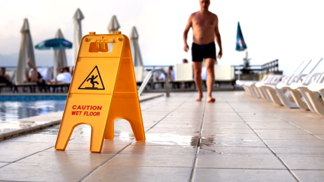 Man walks and fall because of slippery surfaces by yellow wet floor surface warning sign