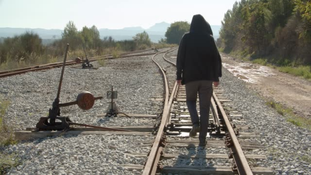 A Man Walks Away By The Railroad Then Turn To The Left