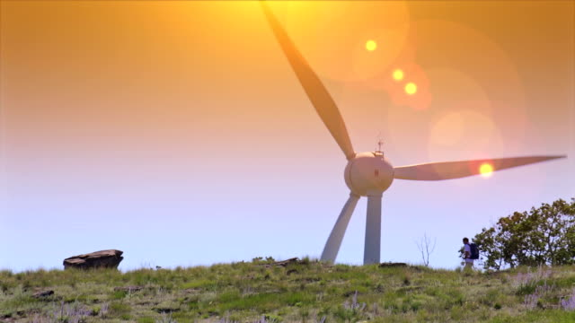 Man walks by a wind turbine video