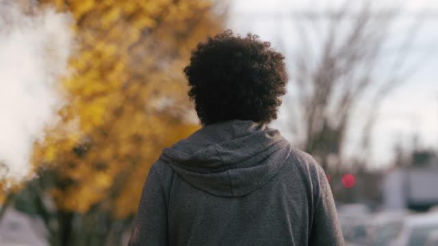un uomo cammina lungo un marciapiede della città mentre fuma uno svapo in una giornata autunnale - sigaretta video stock e b–roll