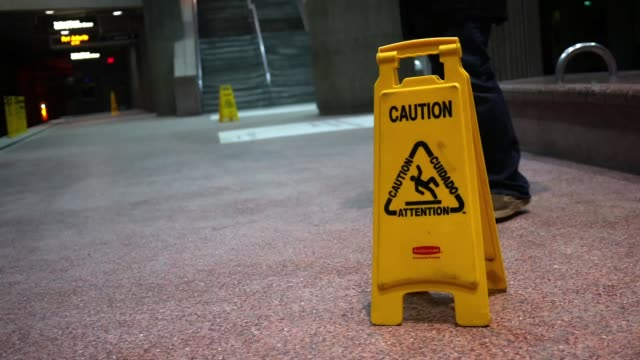 Man walks near a caution falling sign near subway station video