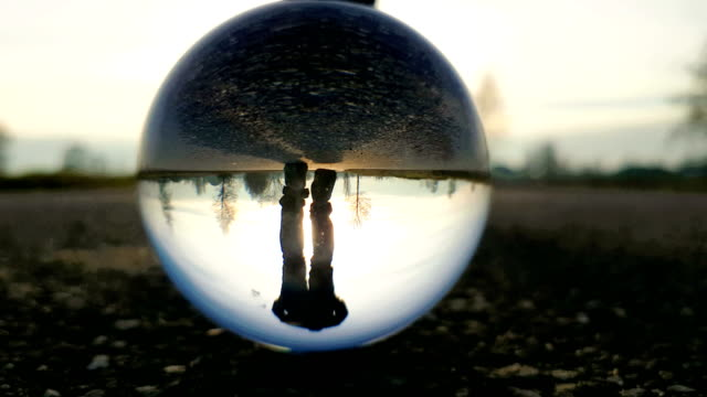 man walks on country road at sunset - filmed through a crystal ball - pedone ruolo dell'uomo video stock e b–roll