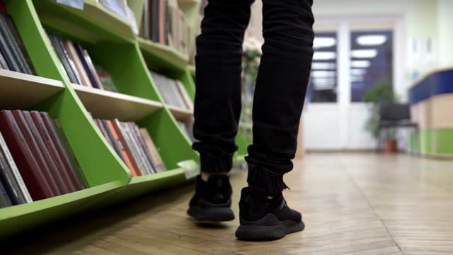 A man walks through the library, looking for a suitable book - vídeo