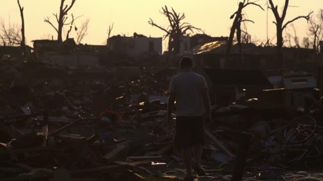 vídeos y material grabado en eventos de stock de hombre camina por daños silohette tornado - tornado