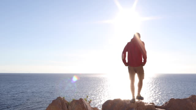 Man walks to cliff edge, sea far below He looks off to distant scene, then continues walking, Liguria pedal pushers stock videos & royalty-free footage