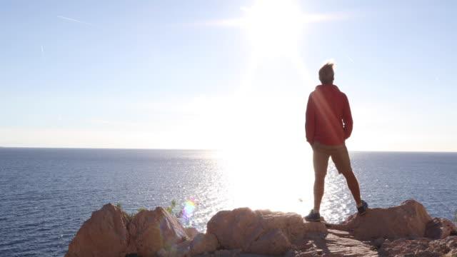 man går till cliff edge, havet långt nedanför - endast en medelålders man bildbanksvideor och videomaterial från bakom kulisserna