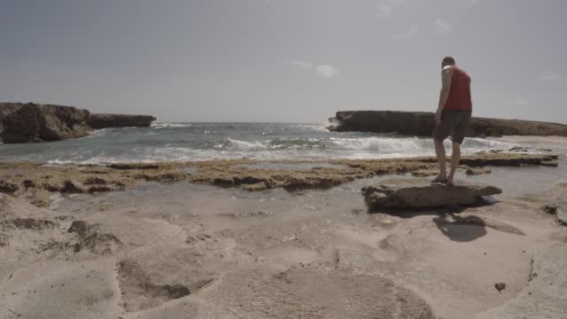 stockvideo's en b-roll-footage met man loopt omhoog naar uitkijk op rotsachtige strand - alleen één mid volwassen man