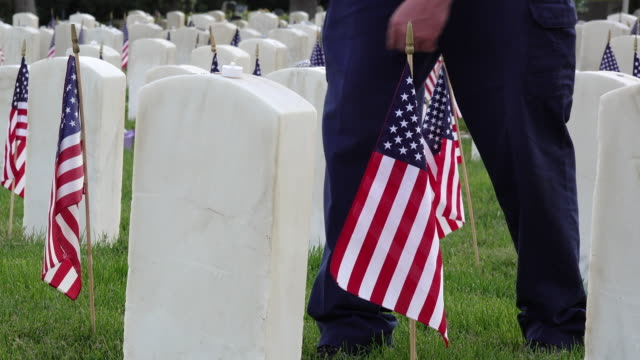 Man Walks up to Military Headstone