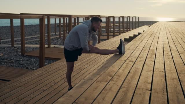 man warming up with leg stretch exercise outdoor at sunset - rozgrzewka filmów i materiałów b-roll