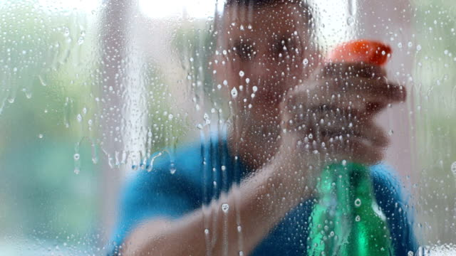 A man washes and wipes the windows of the house