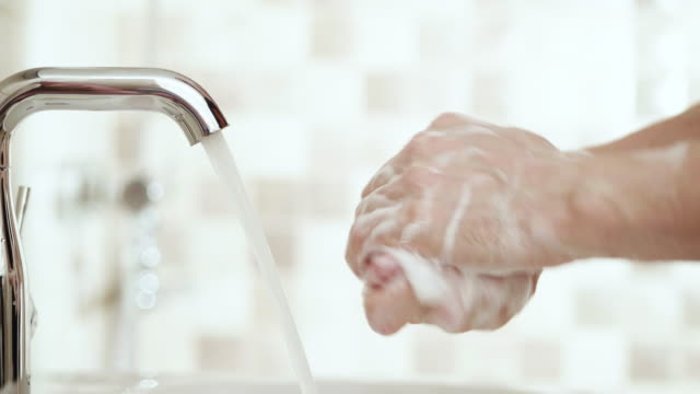 4K - Man washes hands. Close-up