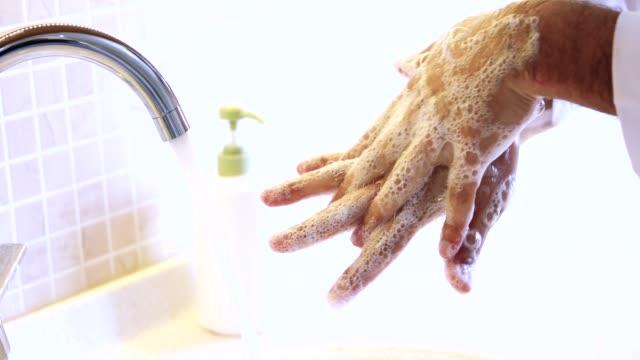 man tvättar händerna ordentligt med tvål som ska skyddas för coronavirus 2019-ncov pandemiepidemisk infektion. - formell klädsel bildbanksvideor och videomaterial från bakom kulisserna
