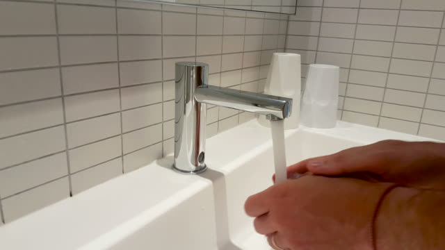 man washing hands with automatic faucet - lavandino video stock e b–roll