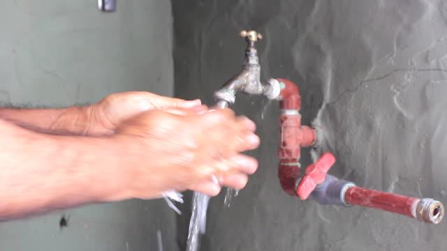 vídeos de stock e filmes b-roll de man washing his hands in a poor bathroom - foam - dedo humano