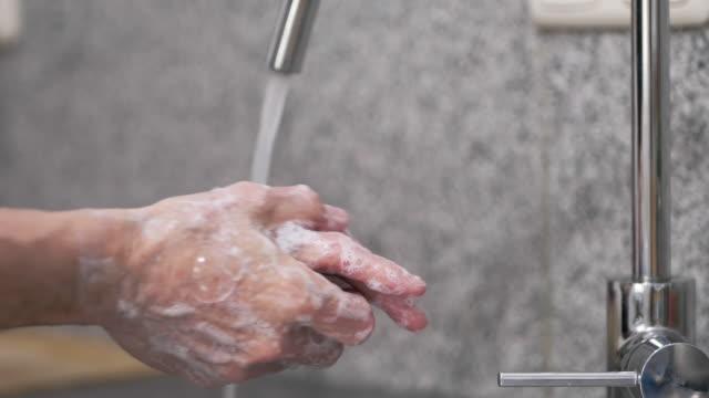vidéos et rushes de homme lavant ses mains dans un évier - laver