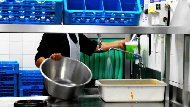 vídeos de stock e filmes b-roll de man washing the utensils in a commercial kitchen - utensílio