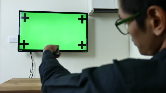 Man Watches Green Mock-up Screen TV Man Watches Green Mock-up Screen TV changing channels stock videos & royalty-free footage