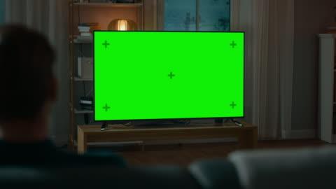 vidéos et rushes de homme montres green maquette écran tv tout en étant assis sur un canapé à la maison le soir. salle de séjour confortable avec des lumières chaudes. sur le coup de l'épaule. - format hd