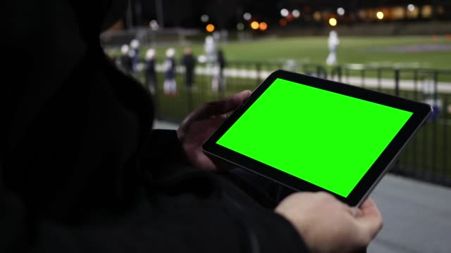 Man watches Green Screen Tablet at a Football Team Practice Session from the bleachers - Close up angle video