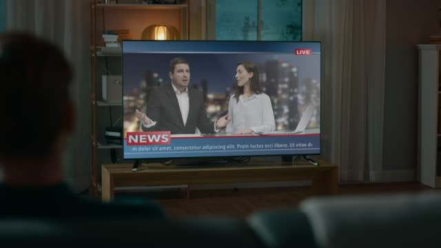 男時計レイトナイト ニュース ショー夕方、自宅でソファに座ってテレビに。2 つのプレゼンターと話をテレビで冗談します。温かみのある照明で居心地の良いリビング ルーム。上肩のショ� - 政治点の映像素材/bロール