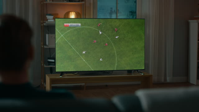 Man Watches Professional Soccer Match on TV while Sitting on a Couch at Home in the Evening. Football Fan Has Fun Watching Sports Event. Over the Shoulder Shot. Man Watches Professional Soccer Match on TV while Sitting on a Couch at Home in the Evening. Football Fan Has Fun Watching Sports Event. Over the Shoulder Shot. Shot on RED EPIC-W 8K Helium Cinema Camera. match sport stock videos & royalty-free footage