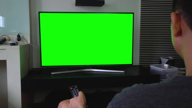 Man watches television green screen on living room video