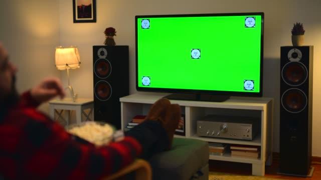 man watching chroma key green screen tv at home - solo un uomo video stock e b–roll