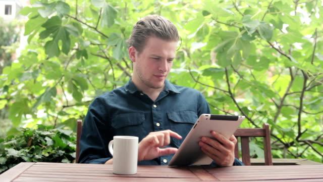 vidéos et rushes de homme regardant drôle vidéo et un avoir un café - man drinking terrace
