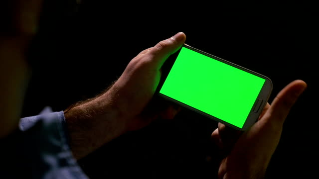 Man watching media content on smart phone with green screen video