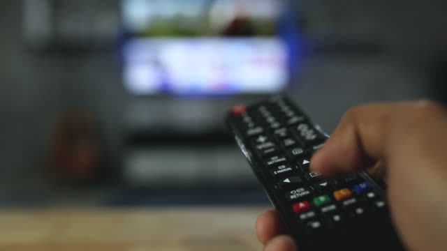 man watching smart tv and using black remote controller on blurred tv background, stay at home concept. - telecomando background video stock e b–roll