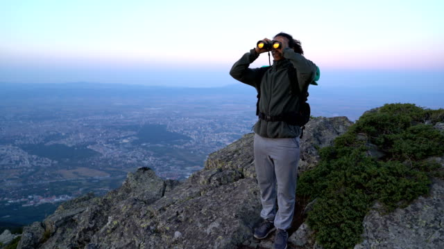 Man watching through binoculars the valley below video
