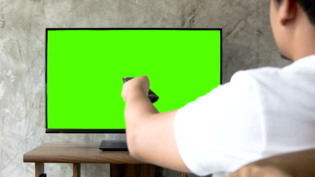 Man watching tv holding remote control. Man watching tv holding remote control,Green Screen. changing channels stock videos & royalty-free footage