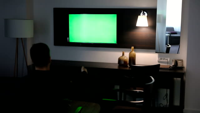 Man watching tv with green screen at hotel room Man watching tv with green screen at hotel room cable tv stock videos & royalty-free footage