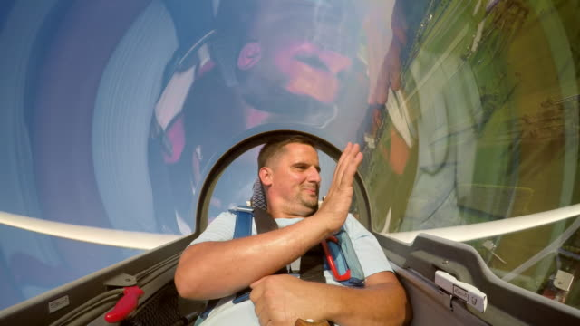 LD Man waving to the ground while sitting in the glider in sunshine