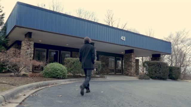 uomo che indossa un cappotto di pisello invernale nero che cammina in un generico edificio commerciale - clinica medica video stock e b–roll