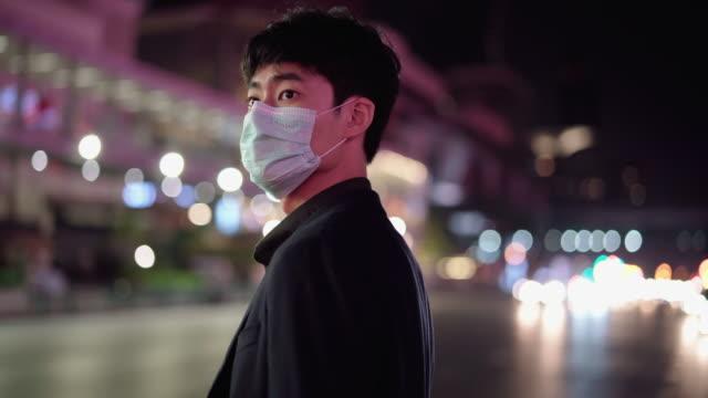 ein mann trägt eine gesichtsmaske und überprüft uber / taxi - smartphone mit corona app stock-videos und b-roll-filmmaterial
