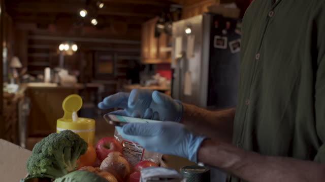 mann mit gesichtsmaske und schutzhandschuhen in seinem lebensmittelgeschäft - smartphone mit corona app stock-videos und b-roll-filmmaterial