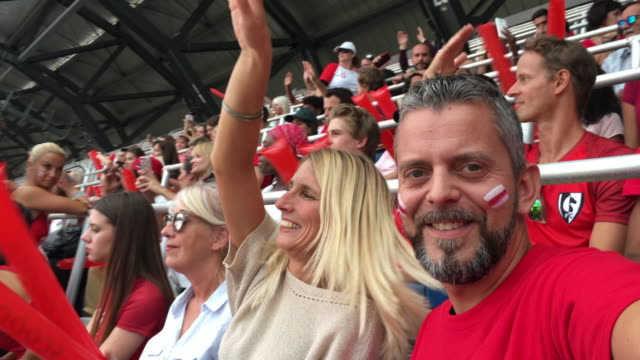 Man wearing a football fan t-shirt making a video of him and his female friend cheering at the stadium