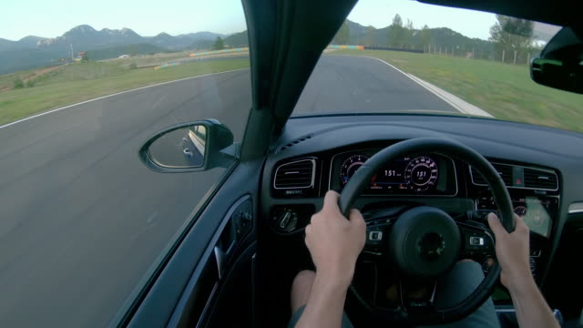 CLOSE UP: Man wearing a helmet races his fast car along the fun racetrack.