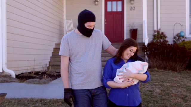 ein mann mit einer sturmhaube hat seinen arm um eine frau mit einem baby - mann tür heimlich stock-videos und b-roll-filmmaterial
