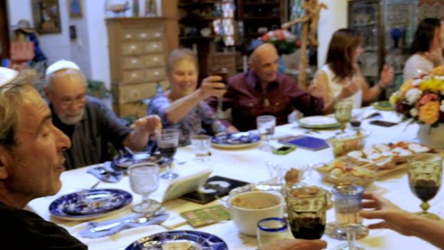 vídeos y material grabado en eventos de stock de un hombre con un yarmulke lleva un brindis en una gran mesa de la cena - pascua judía