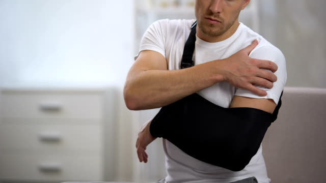 Man wearing arm sling feeling pain in shoulder, result of trauma, orthopedics Man wearing arm sling feeling pain in shoulder, result of trauma, orthopedics physical injury stock videos & royalty-free footage