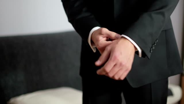 mezzo girato uomo che indossa abito nero regolazione dei polsi, sezione medio - manica video stock e b–roll