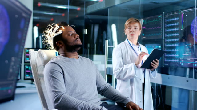 man wearing brainwave scanning headset sits in a chair while scientist with tablet computer supervises process. in the modern brain study laboratory monitors show eeg reading and brain model. - apparecchiatura medica video stock e b–roll